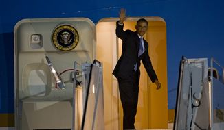 U.S. President Barack Obama waves as he boards Air Force One at John F. Kennedy International Airport in New York, Tuesday, March 11, 2014, after attending a pair of Democratic fundraisers. (AP Photo/Craig Ruttle)