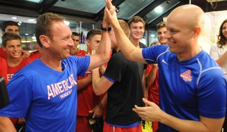 "American University soccer coach Todd West, left, high-fives Shawn Kuykendall, right, at a ""Kuykenstrong"" event. Kuykendall, a former AU and D.C. United player, died March 12, 2014 after a battle with cancer. (American University)"