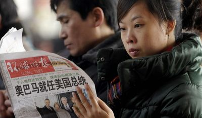 "Agence France-Presse/Getty Images A woman reading a newspaper on Wednesday in Beijing will not find President Obama's entire speech; the state news agency cut a reference to facing down ""fascism and communism."""