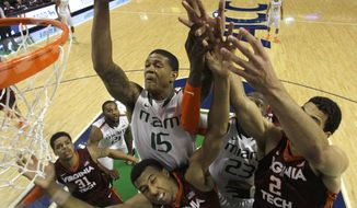 Miami's Rion Brown (15) goes over Virginia Tech's Trevor Thompson (32) and Joey Van Zegeren (2) during the first half of a first round NCAA college basketball game at the Atlantic Coast Conference tournament in Greensboro, N.C., Wednesday, March 12, 2014. (AP Photo/Bob Leverone)
