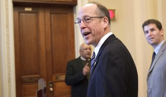 **FILE** Rep. Greg Walden, Oregon Republican, smiles as he heads to the House Ways and Means Committee room on Capitol Hill in Washington on Feb. 16, 2012, to join the bipartisan House and Senate conferees in signing the the compromise agreement. (Associated Press)