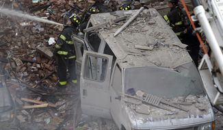 Firefighters respond to a fire on 116th Street in Harlem after a building exploded in huge flames  leading to the collapse of at least one building and several injuries, Wednesday, March 12, 2014, in New York. (AP Photo/John Minchillo)