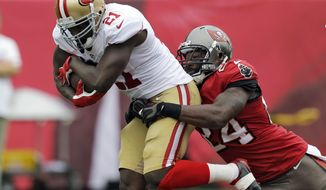 FILE - In this Dec. 15, 2013, file photo, San Francisco 49ers running back Frank Gore (21) is grabbed by Tampa Bay Buccaneers cornerback Darrelle Revis (24) during the first quarter of an NFL football game in Tampa, Fla. The Buccaneers have parted ways with Revis, releasing the five-time Pro Bowl cornerback Wednesday, March 12, 2014, after being unable to trade him and his $16 million annual salary. (AP Photo/Chris O'Meara, File)