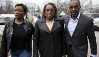 Pennsylvania state Sen. Leanna Washington, center, walks to the police station, Wednesday, March 12, 2014, in Abington, Pa. State prosecutors filed charges alleging Washington used her staff to organize an annual political fundraiser on taxpayer time, using taxpayer resources. (AP Photo/Matt Rourke)