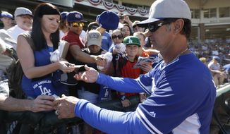 Los Angeles Dodgers manager Don Mattingly signs autographs for fans before a spring exhibition baseball game against the Kansas City Royals on Tuesday, March 11, 2014, in Surprise, Ariz. (AP Photo/Darron Cummings)