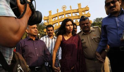 FILE - In this Tuesday, Jan. 14, 2013 file photo, diplomat Devyani Khobragade, center, arrives at Chaitya Bhoomi, a memorial to Indian freedom fighter B.R. Ambedkar, with her father Uttam Khobragade in Mumbai, India. On Wednesday, March 12, 2014, Devyani Khobragade, the deputy consul general for India in New York whose arrest and strip search spurred an international flap, had charges against her dismissed by a federal judge. The judge's ruling said she had diplomatic immunity when she was indicted on charges of fraudulently obtaining a work visa for her housekeeper and lying about the maid's pay. But the ruling leaves open the possibility prosecutors could bring a new indictment against her. (AP Photo/Rajanish Kakade)