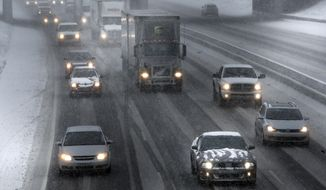 Traffic moves on Interstate 94 during a snow storm in Detroit, Wednesday, March 12, 2014. The storm will likely move the Detroit area close to the seasonal snow total of 93.6 inches set in 1880-1881, according to the National Weather Service. (AP Photo/Paul Sancya)
