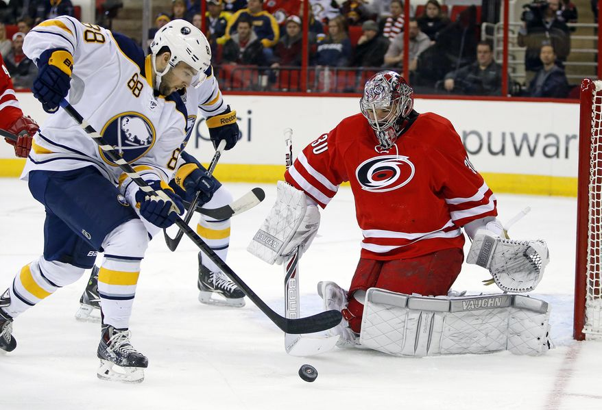 Carolina Hurricanes goalie Cam Ward (30) blocks the shot of Buffalo Sabres' Cory Conacher (88) during the first period of an NHL hockey game in Raleigh, N.C., Thursday, March 13, 2014. (AP Photo/Karl B DeBlaker)