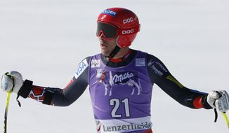 Bode Miller, of the United States, stands in the finish area after taking third place in the men's alpine skiing Super-G at the World Cup finals in Lenzerheide, Switzerland, Thursday, March 13, 2014.  (AP Photo/Marco Trovati)