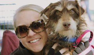 This undated photo provided by Dallas Pets Alive shows Leslie Sans with dog Ethan during an adoption event held in Dallas. Dallas Pets Alive, a non-profit with 12 main volunteers and a pool of 50 foster homes, runs the rescue out of Sans' home. The non-profit's new social media campaign takes Instagram photos of both the celebrities and edits in a dog in need, often attaching humorous captions urging adoptions. (AP Photo/Dallas Pets Alive, Leslie Sans)