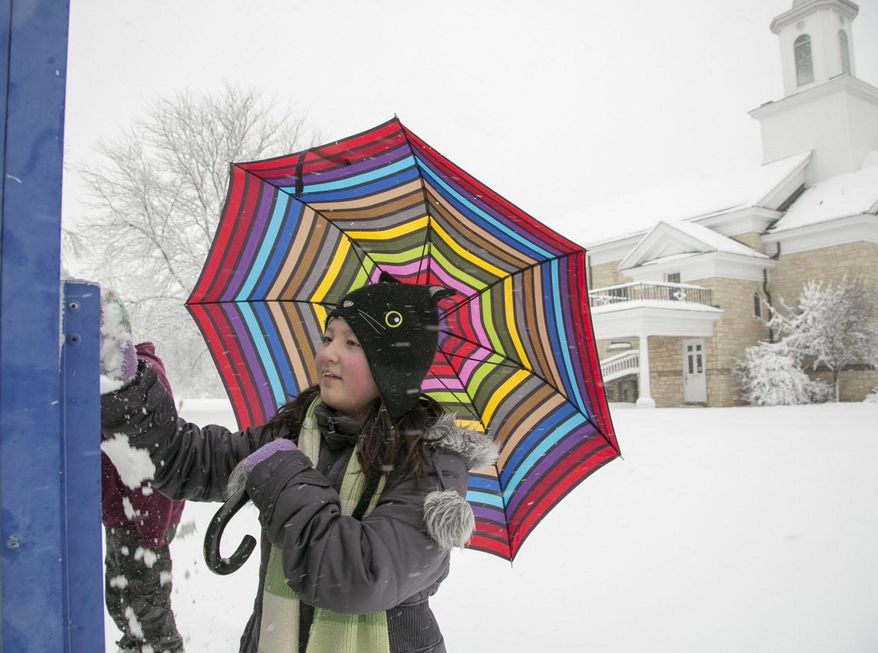 Hana Quinn, 10, wipes snow off the sign for the First Christian Church on South Calhoun Street as she holds her umbrella against the falling snow, Fort Wayne, Ind., Wednesday, March 12, 2014. (AP Photo/The Journal Gazette, Chad Ryan)