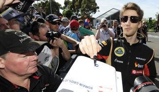 Lotus driver Romain Grosjean of France signs a fan's race program ahead of the Australian Formula One Grand Prix at Albert Park in Melbourne, Australia, Thursday, March 13, 2014. (AP Photo/Andrew Brownbill)