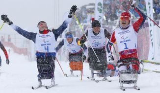 Mariann Marthinsen of Norway, right, celebrates her gold medal as Tatyana Mcfadden of United States, left, reacts to her 2nd place in  final of the women's cross country 1km sprint, sitting event at the 2014 Winter Paralympic, Wednesday, March 12, 2014, in Krasnaya Polyana, Russia. (AP Photo/Dmitry Lovetsky)