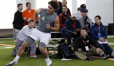 NFL scouts watch as Oklahoma State quarterback Clint Chelf participates in a drill during Oklahoma State's pro day for NFL scouts in Stillwater, Okla., Thursday, March 13, 2014. (AP Photo/Sue Ogrocki)