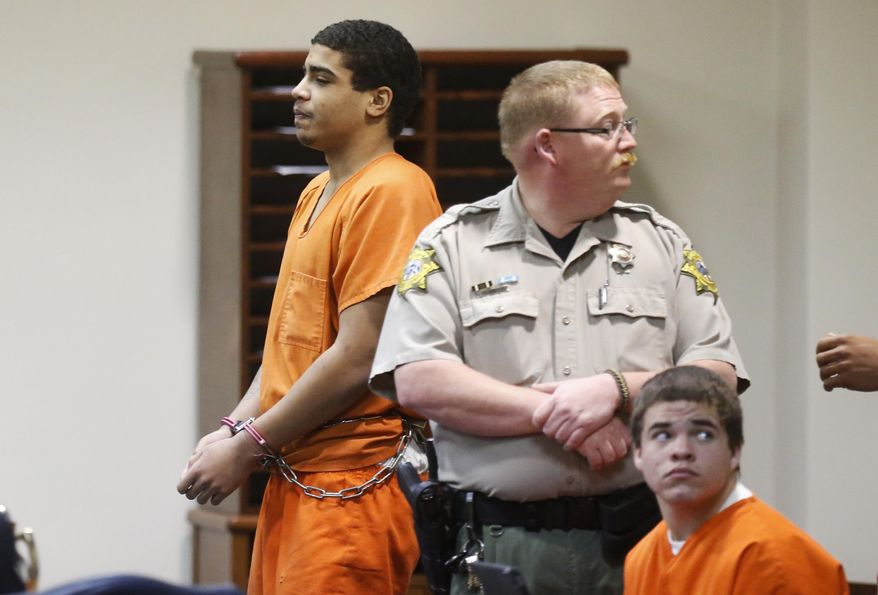 In this photo shot through a courtroom door, defendant Chancey Luna, left, is led from the courtroom following a hearing in Duncan, Okla., Wednesday, March 12, 2014. At right is defendant Michael Jones. Both are charged in the murder of Australian Christopher Lane. (AP Photo/Sue Ogrocki)