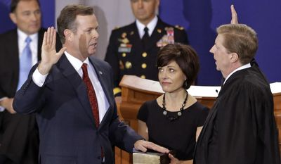 FILE - This Jan. 7, 2013 file photo shows Utah Attorney General John Swallow, left, being sworn in by Chief Justice Matthew B. Durrant, right, at the Utah Sate Capitol Rotunda, in Salt Lake City. A House committee that investigated Swallow has released a final report of its findings Wednesday, March 12, 2014. The report came as the Utah State Bar announced it's been investigating Swallow for over a year after initial allegations against him appeared in the media. (AP Photo/Rick Bowmer, File)