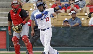 Los Angeles Dodgers' Hanley Ramirez (13) watches his solo home run with Cincinnati Reds catcher Brayan Pena in the fifth inning of a spring exhibition baseball game on Thursday, March 13, 2014, in Glendale, Ariz. (AP Photo/Mark Duncan)