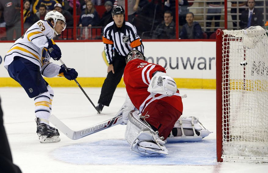 Buffalo Sabres' Tyler Ennis (63) shoots the puck past Carolina Hurricanes goalie Cam Ward (30) to score on a penalty shot during the first period of an NHL hockey game in Raleigh, N.C., Thursday, March 13, 2014. (AP Photo/Karl B DeBlaker)
