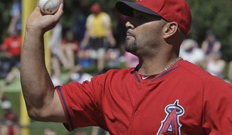 Los Angeles Angels's Albert Pujols bare hands a ball hit by Milwaukee Brewers's Jean Segura during the first inning of an exhibition spring training baseball game Wednesday, March 12, 2014, in Tempe, Ariz. Segura beat the throw to first. (AP Photo/Morry Gash)