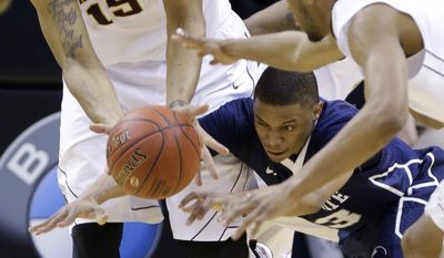 Penn State guard Tim Frazier, center, dives for the loose ball against Minnesota forward Maurice Walker, left, and guard Andre Hollins in the first half of an NCAA college basketball game in the first round of the Big Ten Conference tournament, Thursday, March 13, 2014, in Indianapolis. (AP Photo/Michael Conroy)