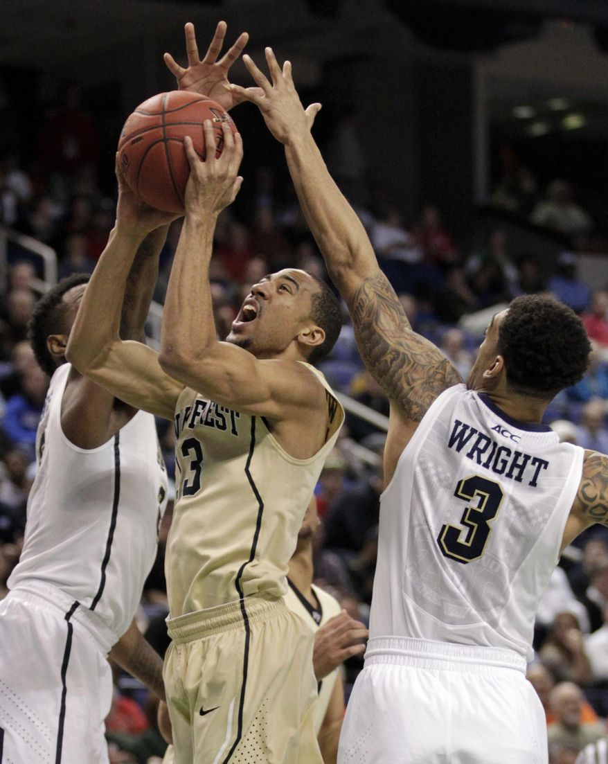 Wake Forest's Coron Williams, center, drive between Pittsburgh's Michael Young, left, and Cameron Wright during the first half of a second round NCAA college basketball game at the Atlantic Coast Conference tournament in Greensboro, N.C., Thursday, March 13, 2014. (AP Photo/Bob Leverone)