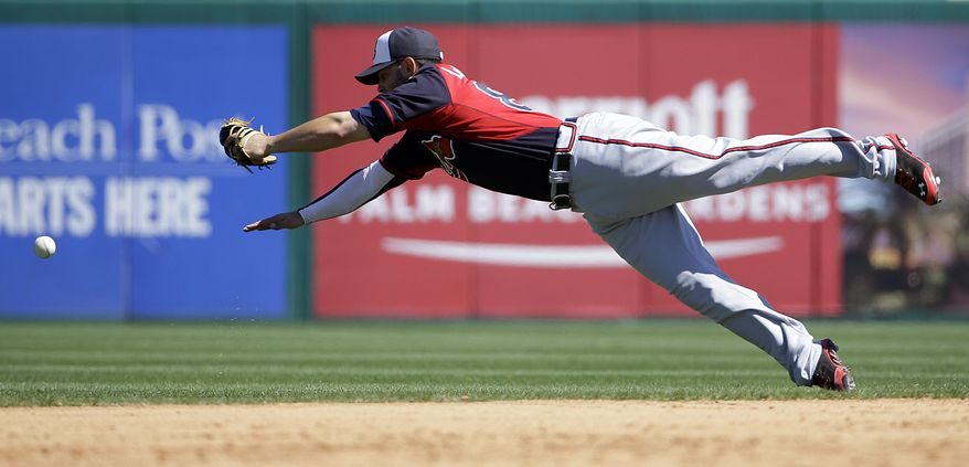 Atlanta Braves' Tommy La Stella dives for a single by St. Louis Cardinals' Peter Bourjos in the sixth inning of an exhibition spring training baseball game, Thursday, March 13, 2014, in Jupiter, Fla. (AP Photo/David Goldman)