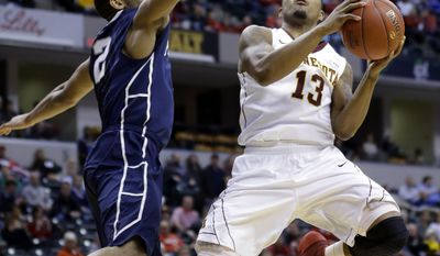 Minnesota guard Maverick Ahanmisi (13) goes up for a shot against Penn State guard D.J. Newbill (2) in the first half of an NCAA college basketball game in the first round of the Big Ten Conference tournament, Thursday, March 13, 2014, in Indianapolis. (AP Photo/Michael Conroy)