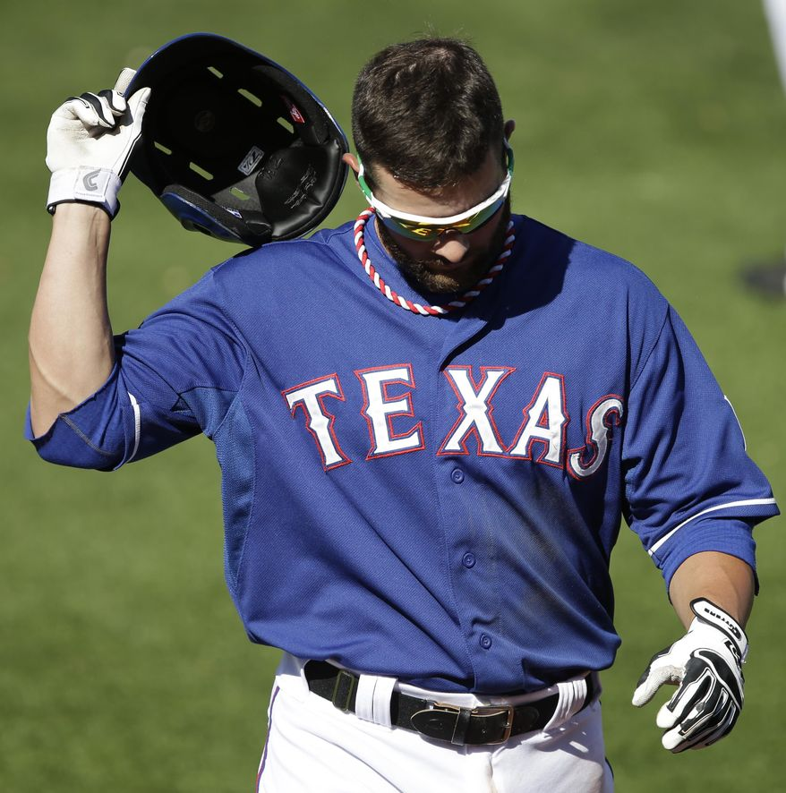 Texas Rangers' Andy Parrino walks back to the dugout after grounding out during the sixth inning of a spring exhibition baseball game against the Los Angeles Angels, Wednesday, March 12, 2014, in Surprise, Ariz. (AP Photo/Darron Cummings)