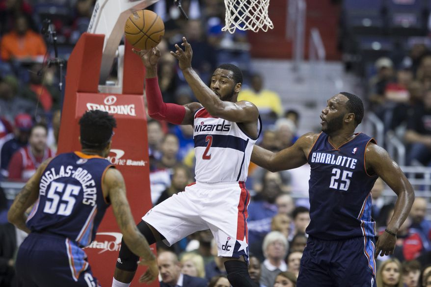 Washington Wizards guard John Wall (2) passes the ball as he is defended by Charlotte Bobcats guard Chris Douglas-Roberts (55) and center Al Jefferson (25) during the first half of an NBA basketball game Wednesday, March 12, 2014, in Washington. (AP Photo/ Evan Vucci)