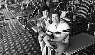 In this photo taken on April 13, 1980, Larry Scott, right, poses with his his wife, Rachel. Scott, a trailblazing bodybuilder who was the first-ever Mr. Olympia, a top international competition, died on March 8, 2014, the Lindquist Mortuary in Bountiful, Utah, said. He was 75. The website for Scott's nutrition supplement company says he died of complications from Alzheimer's disease. (AP Photo/The Salt Lake Tribune, Lynn Johnson)  DESERET NEWS OUT; LOCAL TV OUT; MAGS OUT