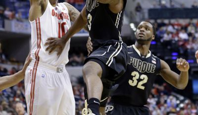 Purdue guard Ronnie Johnson goes up for a shot against Ohio State forward LaQuinton Ross, left, as Purdue forward Errick Peck, right, stands near in the first half of an NCAA college basketball game in the first round of the Big Ten Conference tournament Thursday, March 13, 2014, in Indianapolis. (AP Photo/Michael Conroy)