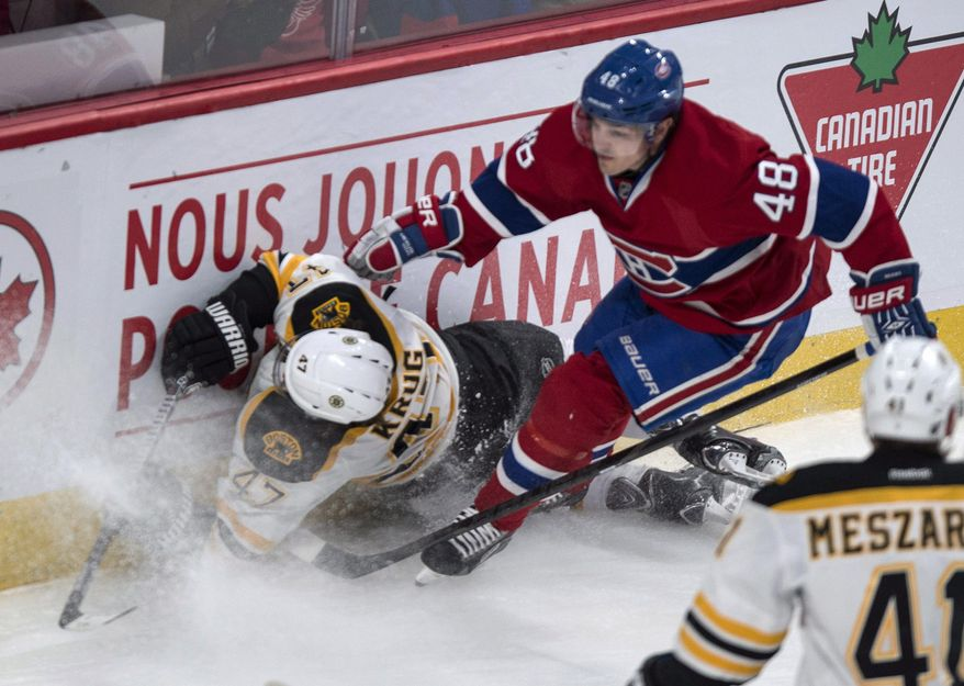 Boston Bruins' Torey Krug crashesinto the boards in front of Montreal Canadiens' Daniel Briere during first period NHL hockey action Wednesday, March 12, 2014 in Montreal. (AP Photo/The Canadian Press, Paul Chiasson)