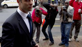 Oscar Pistorius arrives at the high court in Pretoria, South Africa, Wednesday, March 12, 2014. Pistorius is charged with murder for the shooting death of his girlfriend Reeva Steenkamp on Valentine's Day in 2013. (AP Photo/Themba Hadebe)