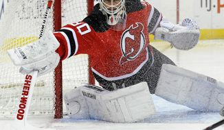 FILE - In this March 4, 2014, file photo, New Jersey Devils goaltender Martin Brodeur deflects the puck during the first period of an NHL hockey game against the Detroit Red Wings in Newark, N.J. Brodeur has re-emerged as the Devils No. 1 goaltender after winning four straight games. (AP Photo/Bill Kostroun, File)