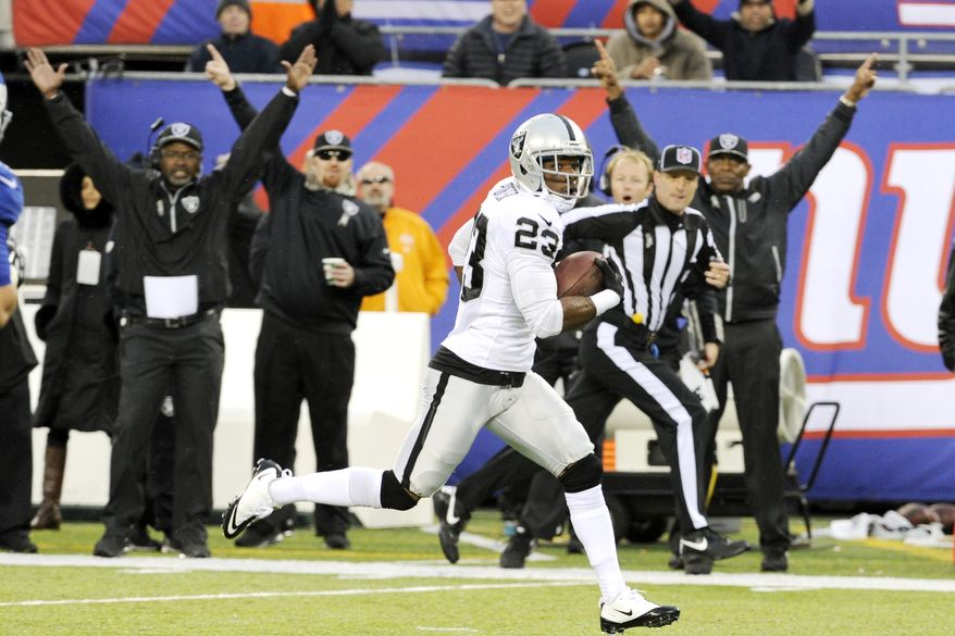 Oakland Raiders cornerback Tracy Porter (23) runs in a touchdown score after intercepting a pass from New York Giants quarterback Eli Manning during the first half of an NFL football game, Sunday, Nov. 10, 2013, in East Rutherford, N.J. (AP Photo/Bill Kostroun)