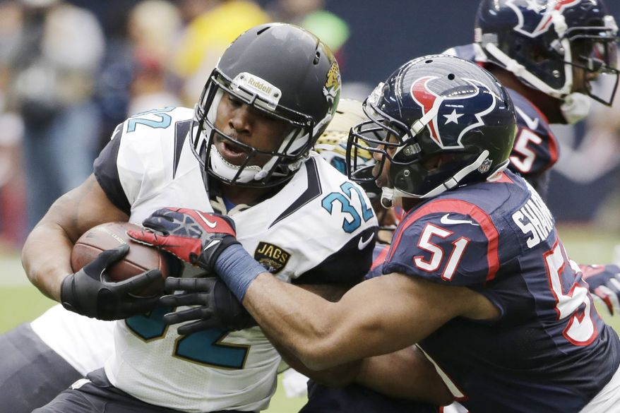 Jacksonville Jaguars running back Maurice Jones-Drew (32) gets tackled by Houston Texans inside linebacker Darryl Sharpton (51) before an NFL football game Sunday, Nov. 24, 2013, in Houston. (AP Photo/David J. Phillip)