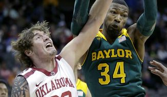 Oklahoma's Ryan Spangler (00) and Baylor's Cory Jefferson (34) battle for a rebound during the first half of an NCAA college basketball game in the Big 12 men's tournament on Thursday, March 13, 2014, in Kansas City, Mo. (AP Photo/Charlie Riedel)