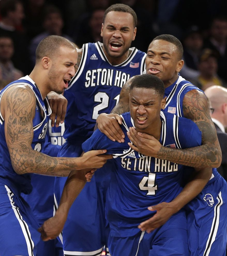Teammates mob Seton Hall's Sterling Gibbs (4) after he hit the winning shot during the second half of an NCAA men's college basketball game against Villanova in the second round of the Big East tournament at Madison Square Garden, Thursday, March 13, 2014 in New York. Seton Hall defeated Villanova 64-63.(AP Photo/Seth Wenig)