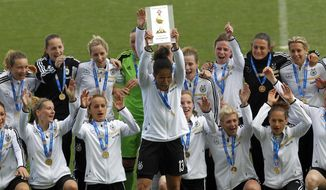 Germany's captain Celia Sasic, center, lifts up the trophy to celebrate with teammate after winning the women's soccer Algarve Cup at the Algarve stadium, outside Faro, southern Portugal, Wednesday, March 12, 2014. (AP Photo/Francisco Seco)