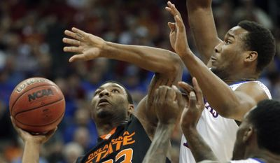 Oklahoma State guard Marcus Smart (33) shoots while covered by Kansas guard Wayne Selden, Jr. (1) and forward Jamari Traylor, right, during the first half of an NCAA college basketball game in the quarterfinals of the Big 12 Conference men's tournament in Kansas City, Mo., Thursday, March 13, 2014. (AP Photo/Orlin Wagner)