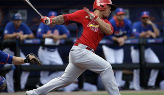 St. Louis Cardinals' Kolten Wong hits a single in the second inning of an exhibition spring training baseball game against the New York Mets, Wednesday, March 12, 2014, in Port St. Lucie, Fla. (AP Photo/David Goldman)