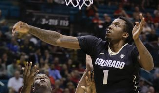 Colorado's Wesley Gordon (1) blocks a shot by California's Jabari Bird (23) in the first half of an NCAA college basketball game in the Pac-12 men's tournament, Thursday, March 13, 2014, in Las Vegas. (AP Photo/Julie Jacobson)