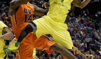 Oregon's Dominic Artis (1) grabs a rebound from Oregon State's Daniel Gomis in the first half of an NCAA college basketball game in the Pac-12 men's tournament, Wednesday, March 12, 2014, in Las Vegas. (AP Photo/Julie Jacobson)