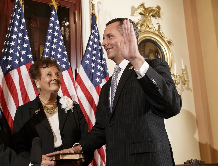 Newly elected Republican Rep. David Jolly of Florida, right, poses for a ceremonial swearing-in with his mother Judy Jolly and House Speaker John Boehner of Ohio, on  Capitol Hill in Washington, Thursday, March 13, 2014. Earlier this week, Jolly edged out Democrat Alex Sink in a special election that Republicans cast as a referendum on President Barack Obama and his unpopular health care law. The Tampa-area district had been considered a toss-up. Jolly fills the open seat that had been held for decades by Republican C.W. Bill Young who died in October. The 41-year-old Jolly has long experience in Washington, first as an aide to Young and then as a lobbyist. Republicans now hold 233 seats in the House to the Democrats' 199. There are three vacancies. (AP Photo/J. Scott Applewhite)