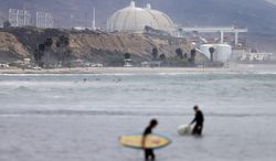 FILE - In this June 7, 2013 file photo, surfers pass in front of the San Onofre nuclear power plant in San Onofre, Calif. More than two years after the San Onofre nuclear power plant stopped production, state regulators planned to make a major decision toward filling the hole left as they consider a proposal on Thursday March 13, 2014. The proposal would allow the plant's co-owners to find replacement power. (AP Photo/Gregory Bull, File)