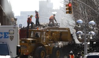Crews secure rubble on a dump truck as debris are removed from the site where two buildings were leveled a day earlier during an explosion, Thursday, March 13, 2014 in New York. Rescuers working amid gusty winds, cold temperatures and billowing smoke pulled four additional bodies Thursday from the rubble of two New York City apartment buildings, raising the death toll to at least seven from a gas leak-triggered explosion that reduced the area to a pile of smashed bricks, splinters and mangled metal. The explosion Wednesday morning in Manhattan's East Harlem injured more than 60 people. (AP Photo/Julio Cortez)