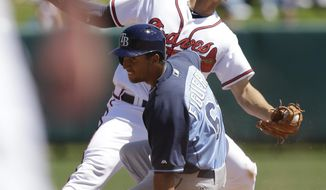 Atlanta Braves shortstop Andrelton Simmons, top, reacts as Tampa Bay Rays' Cole Figueroa slides into second base during the fifth inning of a spring exhibition baseball game in Kissimmee, Fla., Friday, March 14, 2014. Figueroa was out at second after trying to stretch a single into a double.  (AP Photo/Carlos Osorio)