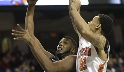 Georgia Tech's Robert Carter, Jr. (4) shoots over Clemson's K.J. McDaniels (32) during the first half of a second round NCAA college basketball game at the Atlantic Coast Conference tournament in Greensboro, N.C., Thursday, March 13, 2014. (AP Photo/Gerry Broome)