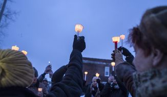 Attendees raise their candles during a vigil at the site of the latest fire at the Heidelberg Project in Detroit, Thursday, March 13, 2014.  A March 7 fire destroyed a house covered in stuffed animals and dolls that was part of the Heidelberg Project. It was the latest casualty in a 10-month string of suspicious fires at houses that are part of the interactive outdoor art installation.  Tyree Guyton founded the Heidelberg Project on Detroit's east side in 1986 as a response to urban decay. (AP Photo/The Saginaw News, Katie Bailey) ALL LOCAL TV OUT; LOCAL TV INTERNET OUT