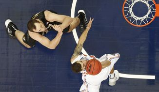 Florida guard Scottie Wilbekin (5) shoots over Missouri forward Ryan Rosburg (44) during the second half of an NCAA college basketball game in the quarterfinal round of the Southeastern Conference men's tournament, Friday, March 14, 2014, in Atlanta. (AP Photo/John Bazemore)
